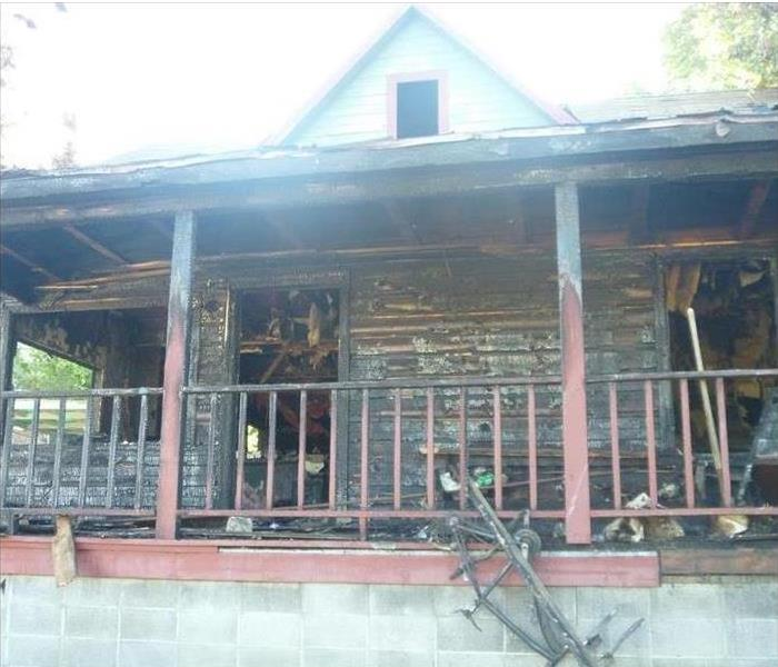 A front view of a wood house severely damaged by fire both inside and out.