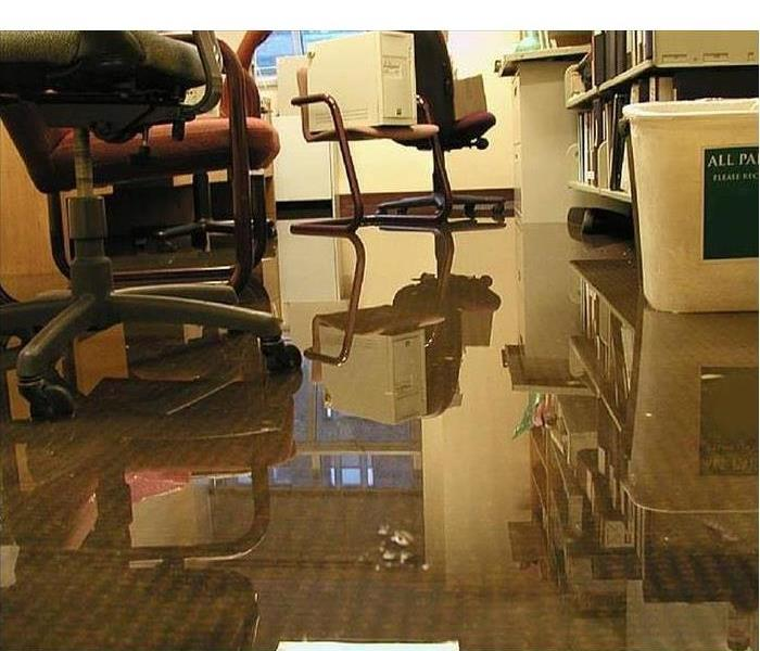 Office space desk and chairs with about one inch of water over carpeting