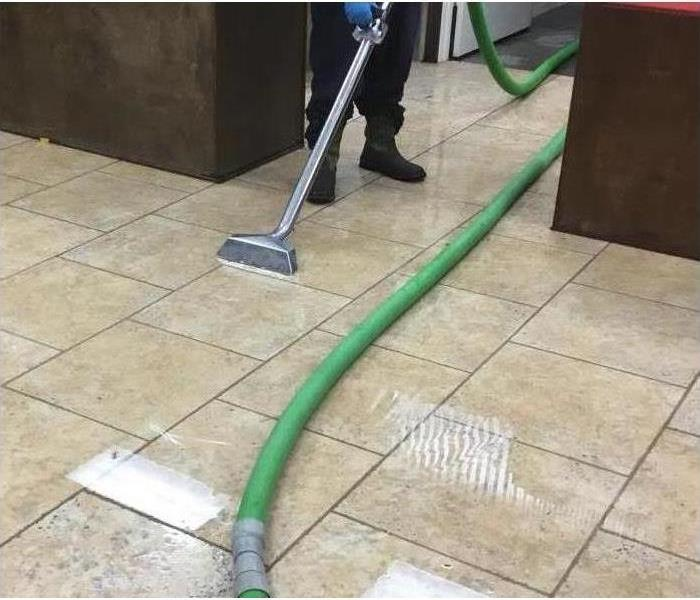 Tile floor with layer of water on it being removed by extraction tool hooked to 3 inch hose