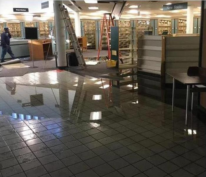 Store in mall with flooded floor and affected ceiling tiles