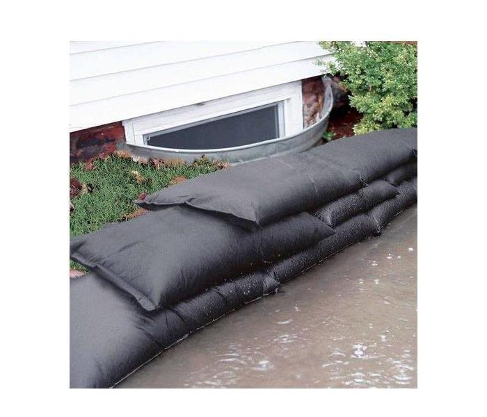 Basement window surrounded by filled sandbags