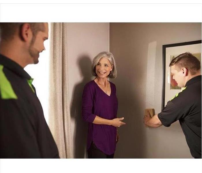 Soot on wall demonstration by two SERVPRO techs for smiling woman
